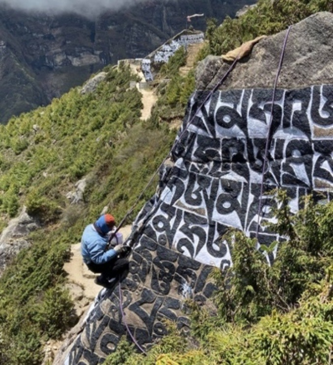 A Sherpa in Namche using his climbing skills to repaint a mani wall during the pandemic